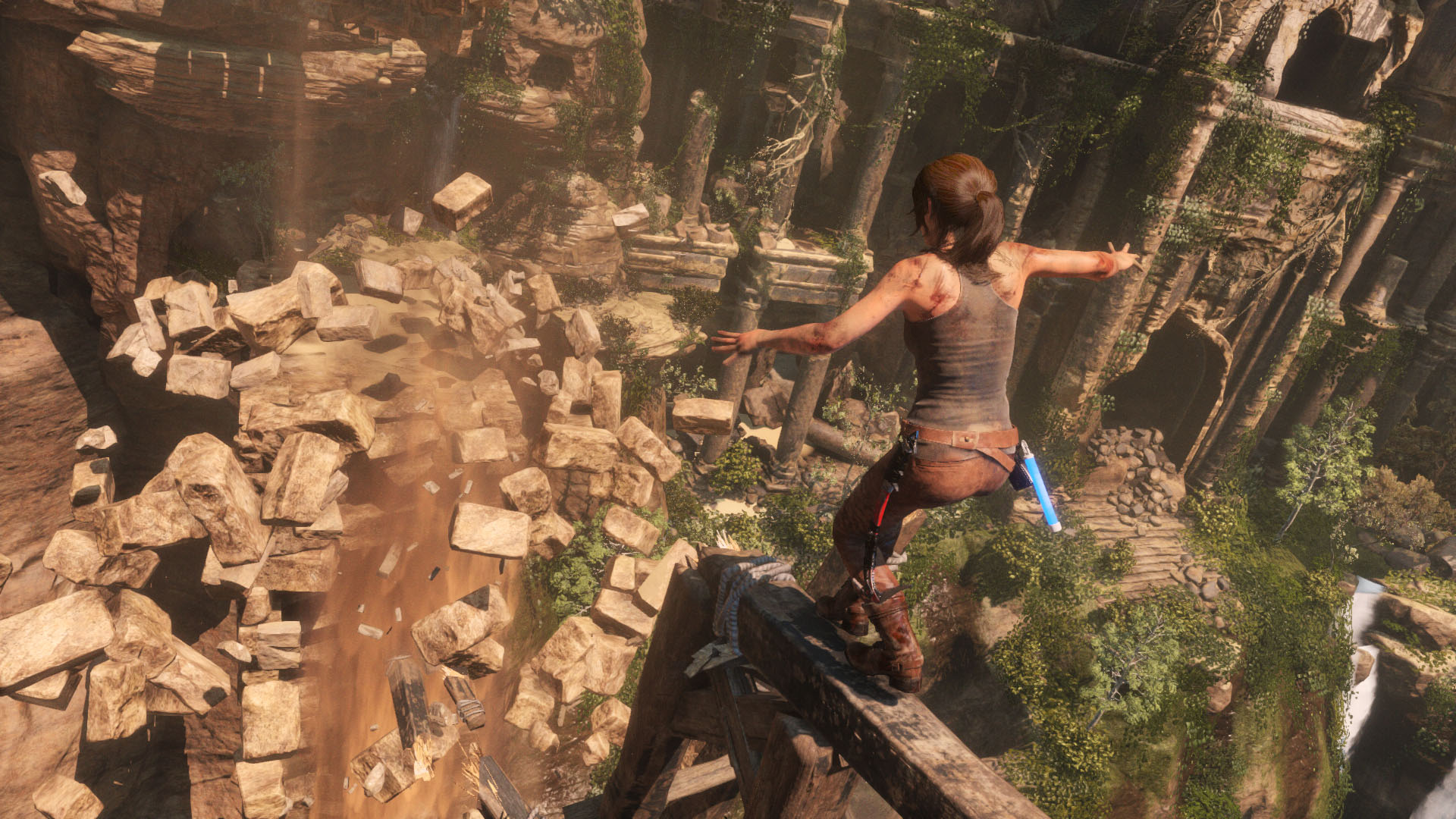 Lara balances herself on a broken beam as the rock platform ahead of her crumbles.